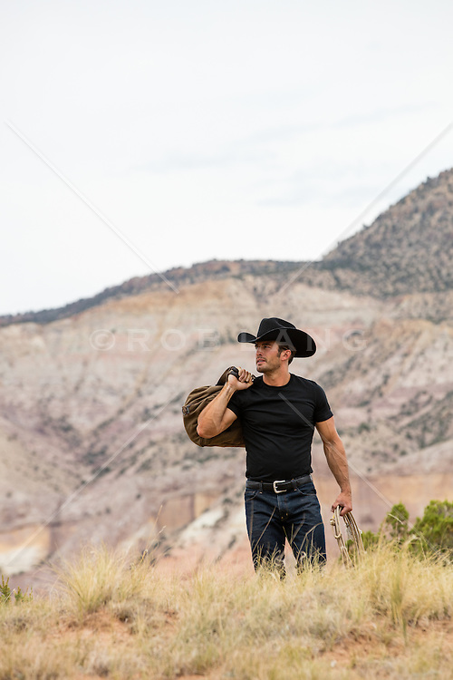 cowboy with a duffle bag walking on a mountain range