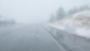 looking through a blurred windshield at unseasonable snowy weather along US 550 near the Continental Divide in NW New Mexico, USA  panorama