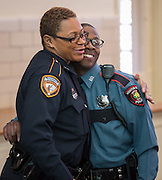 Glenn Nickleson gets a hug from a friend after receiving his badge during a swearing-in ceremony for new officers at the Houston ISD Police Department, March 3, 2014.
