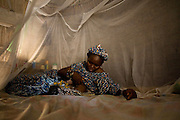A mother breast feeds her baby lie under a mosquito net in their home in the village of Darou Hidjeratou on Tuesday June19, 2007.