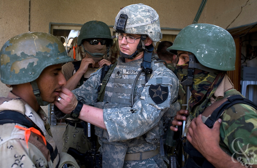 U.S. Army 1-23 Strykers Specialist Nathan Perkins, from Phoenix, AZ helps an Iraqi soldier with his chin strap before a joint house clearing mission in the Mufrek neighborhood of Bacouba, Iraq June 21, 2007.