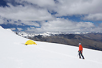Hiker walking toward tent in snowy mountains
