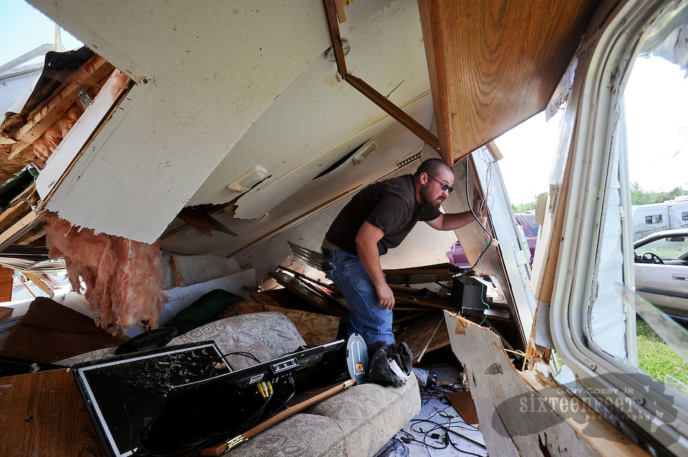 Photo by Gary Cosby Jr.   Residents in Swan Creek, a mobile home community on Highway 31 near Tanner, Ala., recover belongings Thursday, April 28, 2011 left from Wednesday's destructive tornado.  Chad Willis searches through the remains of his mobile home which was rolled and crushed by the storm.