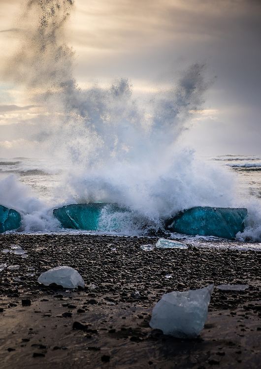 JOKULSARLON, ICELAND - CIRCA MARCH 2015: Waves crashing into an iceberg on the beach near to the Jökulsárlón lagoon in Iceland on the edge of Vatnajökull National Park