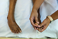 A mother massages her daughters toes after suffering from bed sores during her six month coma Feb 28, 2015. CAMO, Central American Medical Outreach provides medical needs to thousands in and around Honduras, from general medicine, to gynecological, breast exams, basic dental procedures, neurosurgery, plastic surgery, or ophthalmology. Photo Ken Cedeno