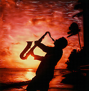 Silhouette of Sax musician playing against intense red sunset Waikiki Beach, Hawaii