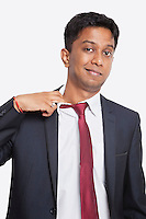 Portrait of tired young Asian businessman against white background