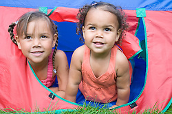 Two little girls playing in a tunnel in the garden,