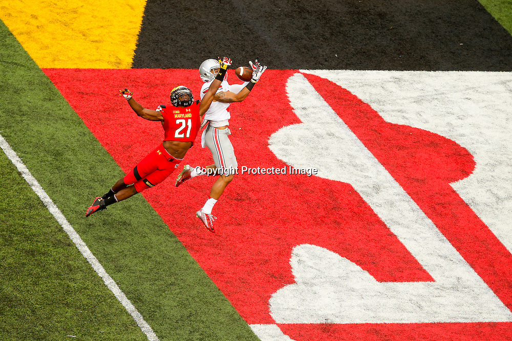 Wide receiver Devin Smith #9 (R) of the Ohio State Buckeyes catches a touchdown pass against safety Sean Davis #21 of the Maryland Terrapins in the third quarter of Ohio State's 52-24 win at Byrd Stadium on October 4, 2014 in College Park, Maryland.