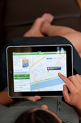 close up of woman using iPad digital tablet computer to read restaurant review in London using Tripadvisor app