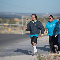 Allen Leal leads the Special Olympics torch run from the McKinley County Sheriff's department in Gallup Monday.