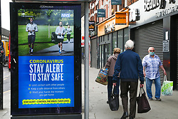 © Licensed to London News Pictures. 22/05/2020. London, UK. People walk past a 'CORONAVIRUS - STAY ALERT TO STAY SAFE' digital poster in north London, which is a part of the government's new public information campaign as the lockdown is eased. Photo credit: Dinendra Haria/LNP