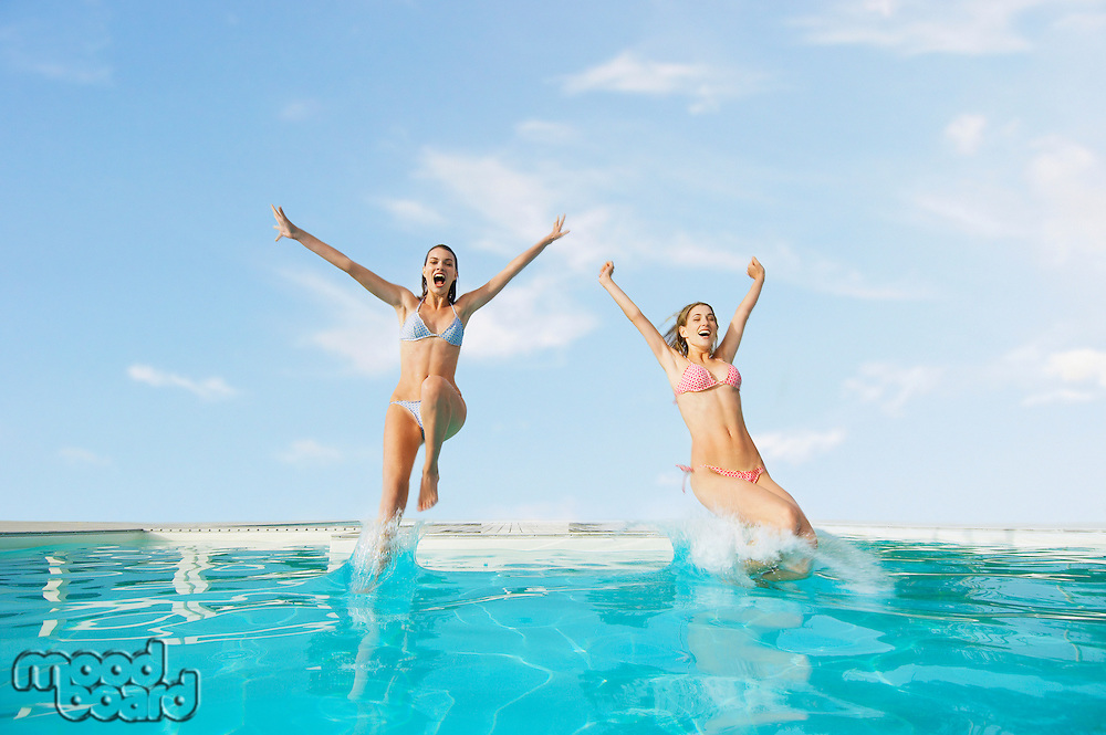 Young Women Jumping into Swimming Pool front view