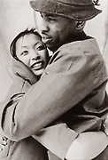 Asian woman and black man hugging, U.K.