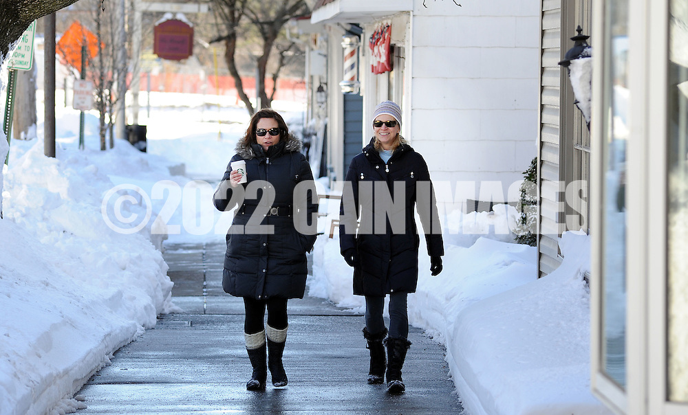 Jill McDade (left) and Michelle Cunningham, both of Newtown, Pennsylvania walk along State Street as the region cleans up after Winter Storm Jonas Sunday January 24, 2016 in Newtown, Pennsylvania. (Photo by William Thomas Cain)