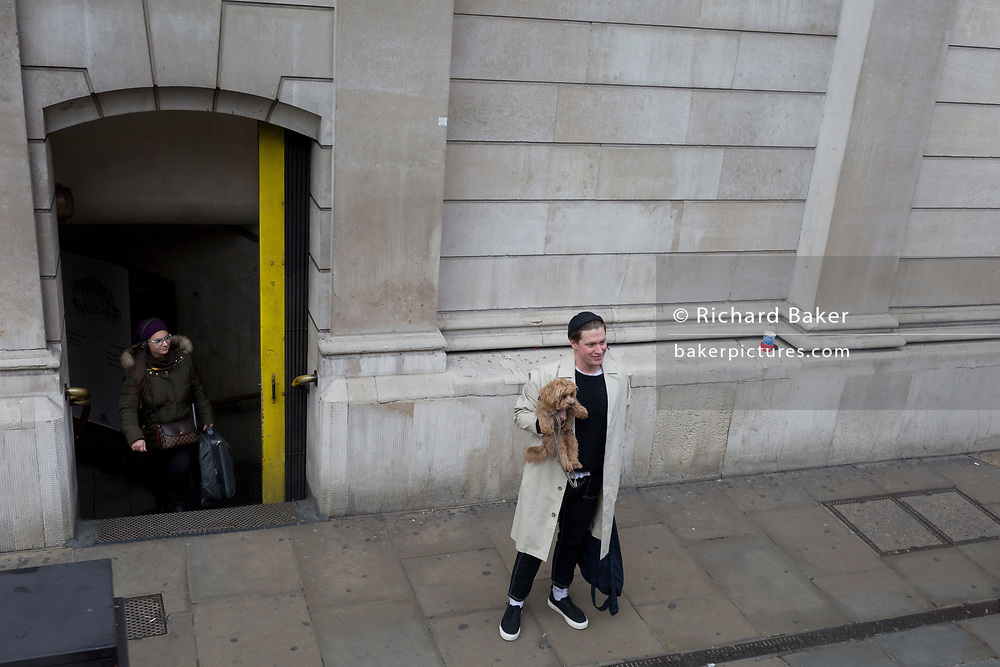 A man holds his pet dog in his arm while standing outside Bank Underground tube station in the City of London, the capital's financial district, on 18th November 2019, in London, England.
