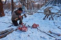 Mongolie, province de Khovsgol, les Tsaatans, éleveurs des rennes, campement en hiver des Tsaatan, decoupage de la viande de renne// Mongolia, Khovsgol province, the Tsaatan, reindeer herder, the winter camp, reindeer meat
