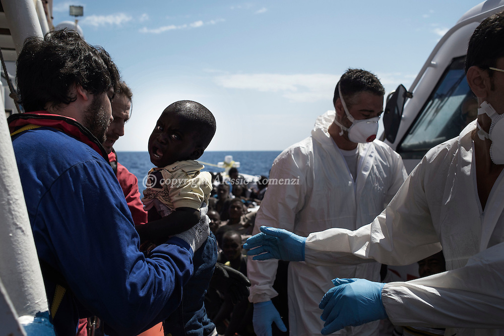 Italy: MSF Dignity1: Italian coastal guard officials pass an African migrant child to Dignity1 crew members on August 23, 2015. Alessio Romenzi