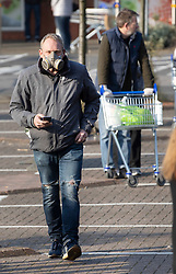 © Licensed to London News Pictures. 28/03/2020. Leatherhead, UK. A shopper wears a builder's face mask for protection as he waits in line for a Tesco store to open in Leatherhead, Surrey. The Prime Minister Boris Johnson and Health Secretary Matt Hancock have tested positive for the virus and are now self isolating. Photo credit: Peter Macdiarmid/LNP
