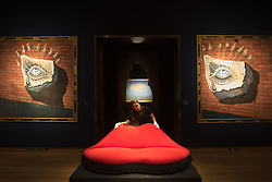 Christie's, London, February 24th 2017. Fine art auctioneers Christie's hold a press preview for their Impressionist and Modern Art and Art of the Surreal sale which takes place on 28th February. PICTURED: A woman poses in the Salvador Dali 'Face' installation comprising three lots, from left to right, L'oeil fleuri, décor pour le ballet Tristan fou painted in 1944 and estimated to fetch between £350,000 - 550,000, Dali's iconic Mae West Lips sofa expected to fetch between £400,000 - 600,000, and a second version of  L'oeil fleuri, décor pour le ballet Tristan fou, again worth between £350,000 and 550,000.