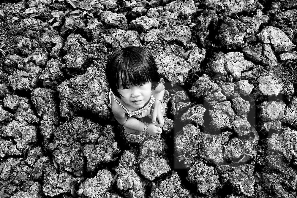 Bird's eye view of a young Vietnamese girl squatting in the dry mud of Tay Ninh Province during a drought, Vietnam, Southeast Asia. Image focused on global warming effects.