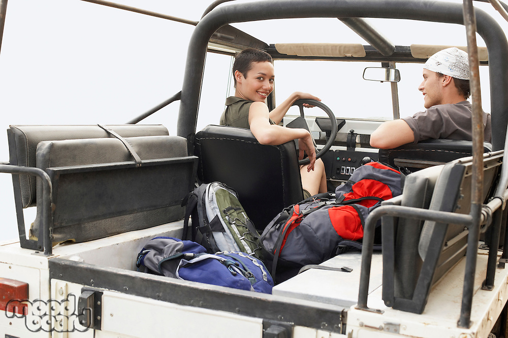 Couple sitting in four wheel drive car outdoors