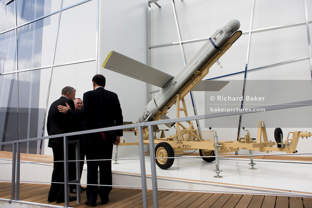 Businessmen inspect the 12ft Fire Shadow missile on manufacturer MBDA's trade stand at the Farnborough airshow. The so-called lurker bomb is designed to loiter above a battlefield for up to 6 hours before attacking stationary or mobile targets and also able to shadow British troops for up to ten hours or 100 miles, ready to take out enemy targets with surgical precision at a minute's notice..