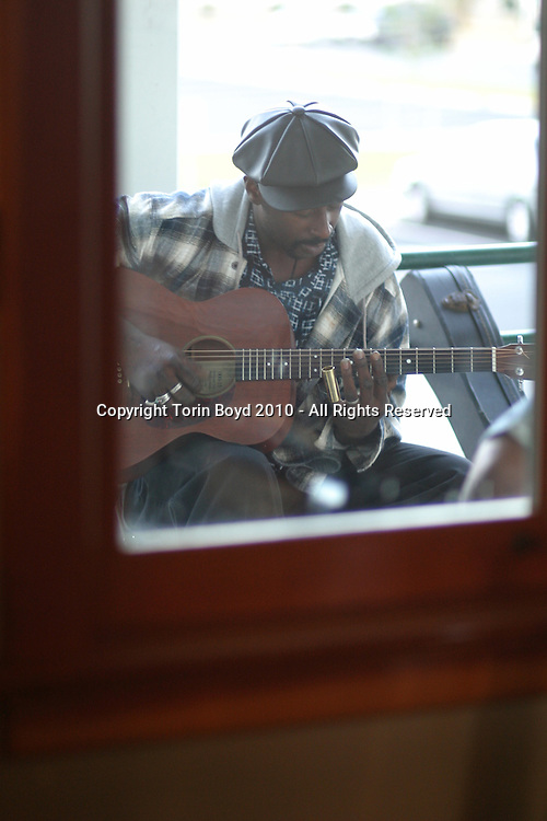 """Eric Freeman is an emerging blues artist from Sperryville, Virginia who specializes in the Piedmont style of blues. His unique high energy style of acoustic guitar playing is helping to preserve the tradition of minstrel songplaying. Freeman is at his best when playing house parties and has studied under the legendary songster John Jackson. Eric is seen here jamming on a back porch during the """"Centrum's Country Blues Workshop"""", in Port Townsend, Washington."""
