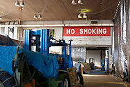 NO SMOKING written for safety purposes during WWII plane maintenance, Mitchel Field airplane hangar, part of historic aviation history; vehicle for moving heavy items in foreground in soft focus. Now used for restoration work by Cradle of Aviation, Long Island air and space museum, on February 8, 2010, in Garden City, New York, USA.