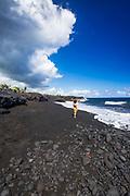 Woman on the new Kaimu black sand beach, Kalapana, The Big Island, Hawaii USA