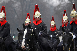 © Licensed to London News Pictures. 23/03/2013, London, UK. Queen's Life Guards ride past Buckingham Palace in the snow in London, Saturday, March 23, 2013. Photo credit : Sang Tan/LNP