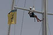 Young man paints mast of boat docked at megayacht pier in Port America's Cup; Valencia, Spain.