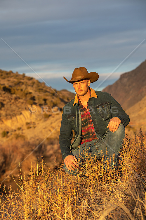 cowboy kneeling down on a mountain top at sunset
