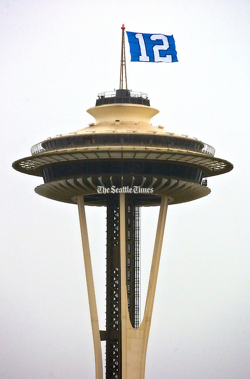 The 12th Man Flag is erected on top of The Space Needle to cheer on the Seattle Seahawks.<br />