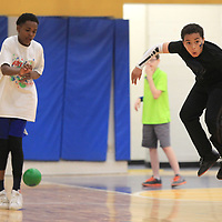 Lynn Shelly, 12, a student at Milam, jumps to avoid being hit while playing dodge ball in the gym at Milam during the school's field day on Monday. The school celebrated the day with inflatables, dodge ball, kickball, snow cones and music.