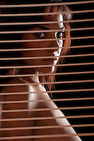 Sensual hispanic woman looking trough a courtain blind.