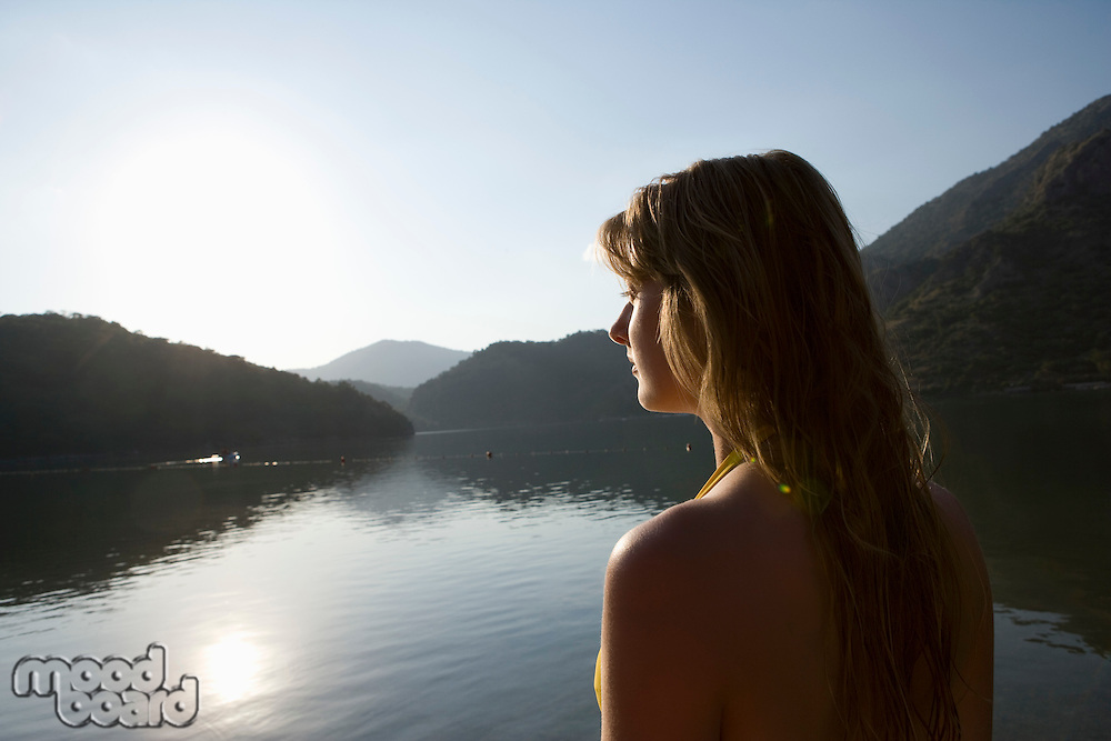 Blonde woman looks out across morning sunrise over lake