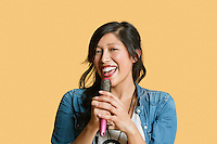 Portrait of a young woman singing into a hairbrush over colored background