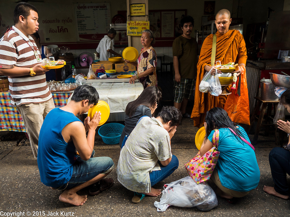 02 SEPTEMBER 2015 - BANGKOK, THAILAND: A Buddhist monk on his morning alms round in Bang Chak Market. The Bang Chak Market serves the community around Sois 91-97 on Sukhumvit Road in the Bangkok suburbs. About half of the market has been torn down, vendors in the remaining part of the market said they expect to be evicted by the end of the year. The old market, and many of the small working class shophouses and apartments near the market are being being torn down. People who live in the area said condominiums are being built on the land.         PHOTO BY JACK KURTZ