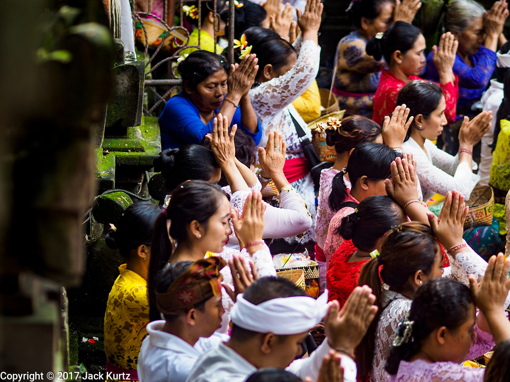 """02 AUGUST 2017 - UBUD, BALI, INDONESIA: Market venders pray in the temple during the """"Merchants' Day"""" ceremony at the Pura (Temple) Melanting Pasar Ubud, the small Hindu temple in the Ubud market. It's a day that merchants throughout Ubud come to the temple to make offerings and pray for prosperity.    PHOTO BY JACK KURTZ"""