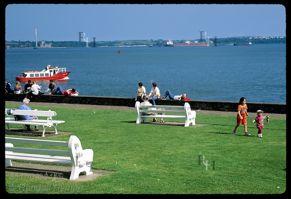 Seafront park overlooks Cork harbor, one of the largest in the world, as ferry passes; Cobh. Ireland