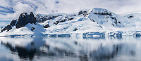 Steep glaciated mountain terrain overlooks Danco Harbour on the antarctic Peninsula.  Antarctica.