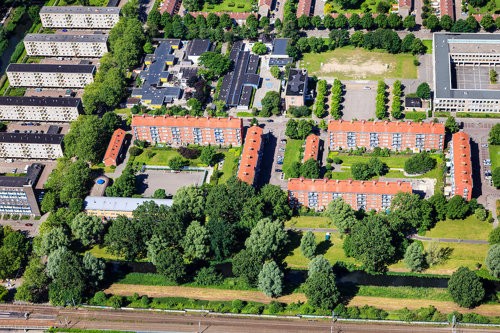 Nederland, Noord-Holland, Amsterdam, 14-06-2012; Slotervaart, flats aan de Jacob Geelstraat, bouwblokken los van elkaar ivm toetreding van de zon. Links de Comeniusstraat. Onder in beeld de ringspoorbaan..De buurt is onderdeel van de Westelijke Tuinsteden, gerealiseerd op basis van het Algemeen Uitbreidingsplan voor Amsterdam (AUP, 1935). Voorbeeld van het Nieuwe Bouwen, open bebouwing in stroken, langwerpige bouwblokken afgewisseld met groenstroken. .This residential area (Slotervaart) is an example of garden cities of Amsterdam-west. Constructed on the basis of the General Extension Plan for Amsterdam (AUP, 1935). Example of the New Building (het Nieuwe Bouwen), detached in strips, oblong housing blocks alternated with green areas, built in fifties and sixties of the 20th century. The housing buildings  (center right) have been placed separately for the accession of sun..luchtfoto (toeslag), aerial photo (additional fee required).foto/photo Siebe Swart
