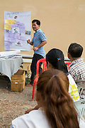 VSO volunteer Giovanni Villafuerte delivering a workshop to around 40 farmers within the Banan co-operative outside their rice warehouse to help them increase their crop yields.  The VSO / Accenture IMA4P project, Banan, Cambodia.
