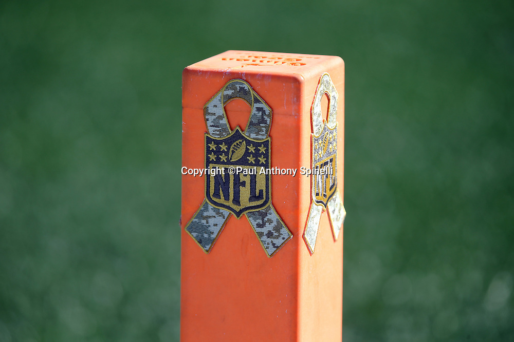 """An end zone pylon is decorated with an NFL logo intertwined with a military logo as part of the """"Salute to Service"""" initiative before the New England Patriots 2015 week 9 regular season NFL football game against the Washington Redskins on Sunday, Nov. 8, 2015 in Foxborough, Mass. The Patriots won the game 27-10. (©Paul Anthony Spinelli)"""
