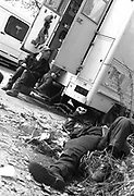 Travellers sitting by van, one passed out on the floor, small kid climbing into back of the van, Bolonga. 2000's,