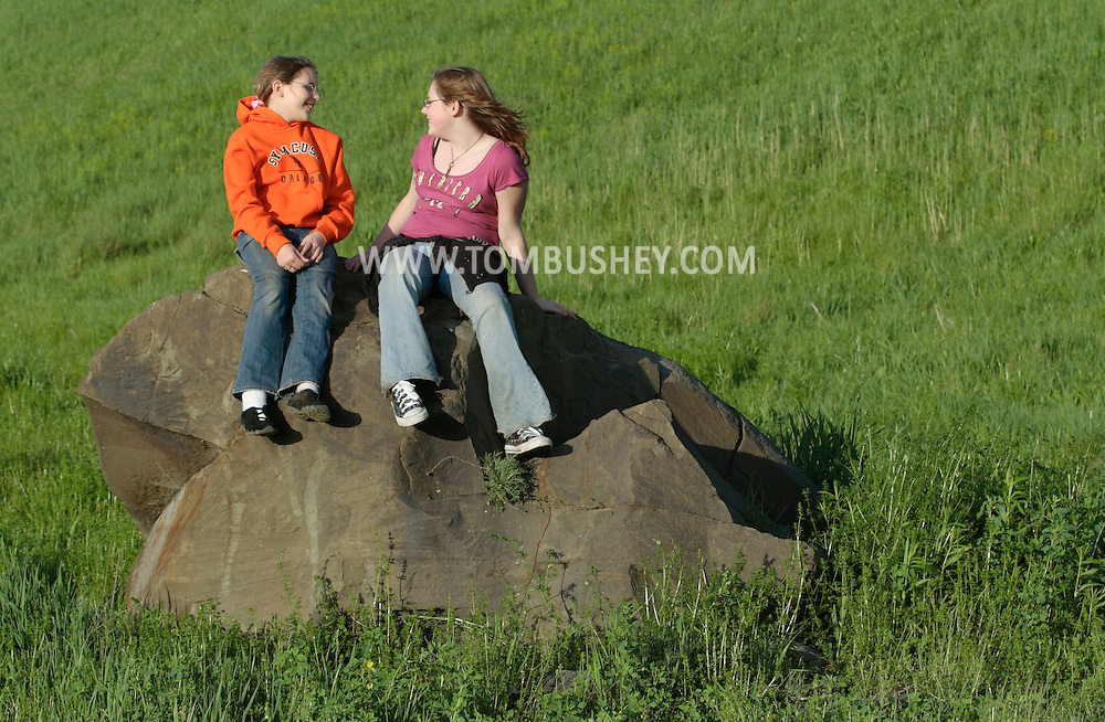Salisbury Mills, NY- A 10-year-old girl and her 12-year-old sister sit on a rock in a field while hiking on May 10, 2009.
