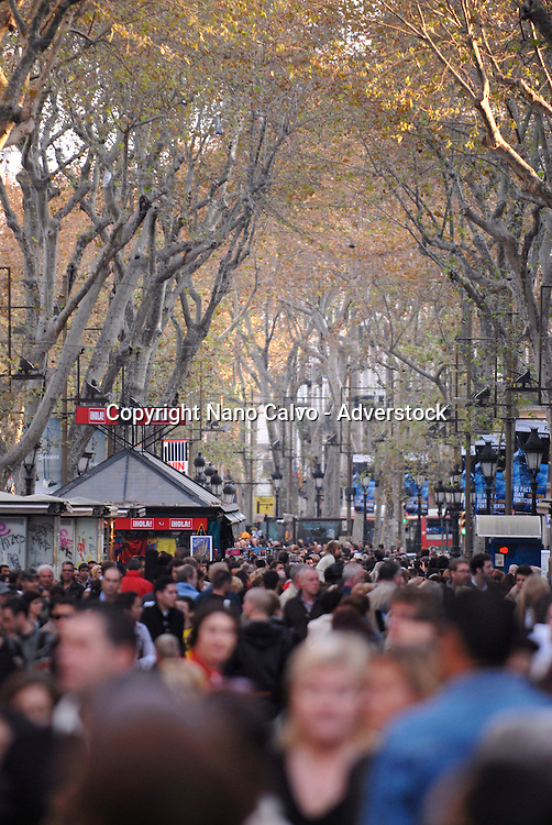 Sunday daylife in popular Ramblas avenue, a crowded street where tourists, performers, artists and citizens get mixed and enjoy a curious walk through one of the best known places in the interesting city of Barcelona, Spain