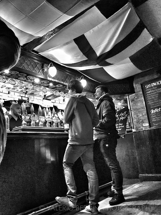 Two guys chat with the pub waiter while getting an ale at the Pickerel Inn pub in Magdalene Street in Cambridge. The ceiling is covered with flags of the teams playing the six nations rugby competition on going these weeks. The day after this image was taken England defeated Wales guaranteeing the victory of 2016 edition of the tournament.