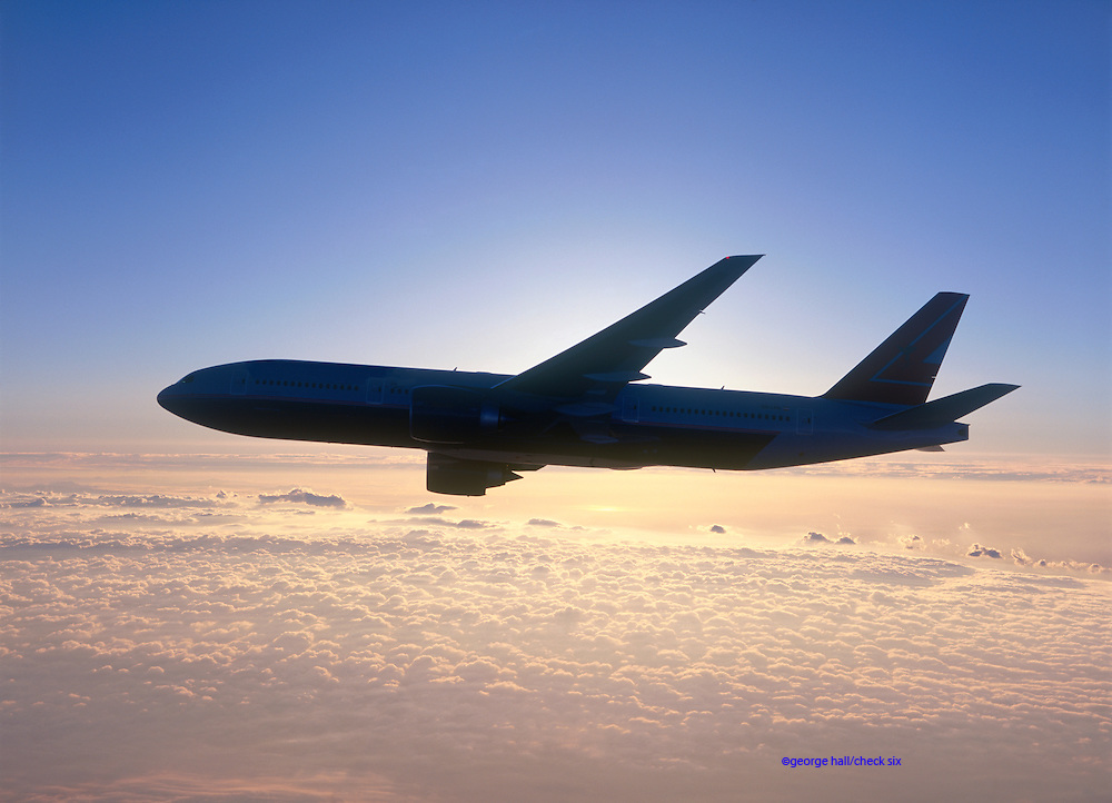 Boeing 777 in silhouette at sunset